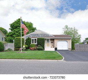 American Flag Suburban bungalow home blue sky clouds USA