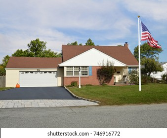 American Flag Suburban bungalow home two car garage blue sky clouds USA