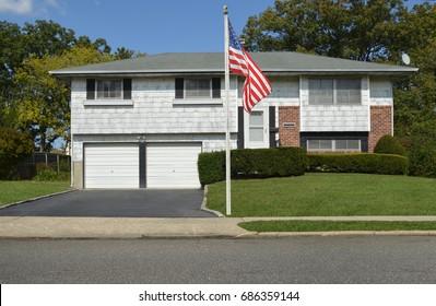 American Flag Suburban high ranch home USA blue sky