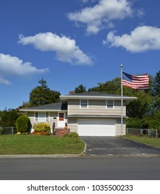 American Flag Suburban Split Level home blue sky clouds USA