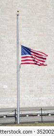 American flag swaying on the pole> white brick on the background brick from Washington Monument structure