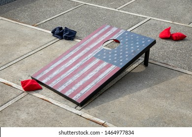 American flag themed corn hole game board with bean bags on the ground, in a backyard game scene with space for text