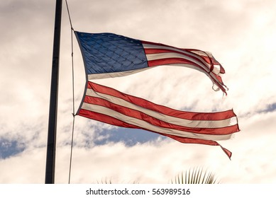 American flag torn down the middle waving in the wind on a cloudy sky.  Resistance.