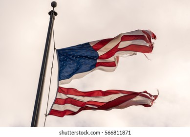 American flag torn down the middle waving in the wind on a cloudy sky. Divided politics.