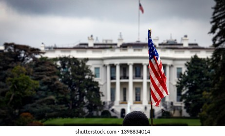 The American flag of a tourist standing in front of the White House in Washington, DC.