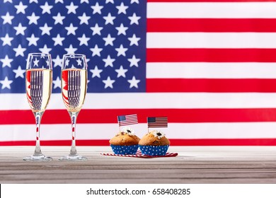 American flag, two glasses of champagne and cute cupcakes