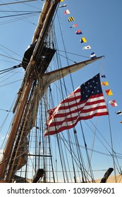 An American flag unfurls in the wind beside the mast and rigging of a historic tall ship. Small  pennants flutter in a line along and above the flag. a clear blue sky completes the background.