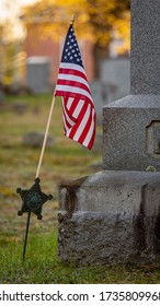 An American flag in a Veteran's flag holder next to a granite headstone.