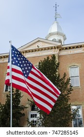 An American flag waves in the wind in front of a nondescript Victorian era courthouse.  The cupola, weathervane and gingerbread trim on the courthouse give a sense of history.