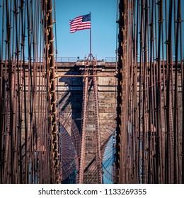 The American flag waving above a New York City bridge.