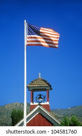 American flag waving above one room schoolhouse, Wellington, NV