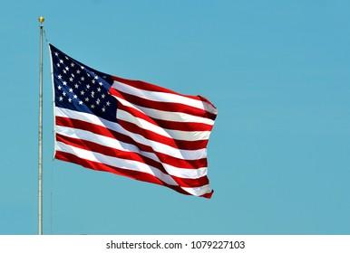 American Flag waving against clear blue sky