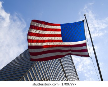 American flag waving against a skyscraper an a blue sky.