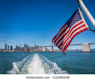 American flag waving in front of San Francisco skyline and the Bay Bridge