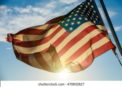American Flag Waving in front of sun.