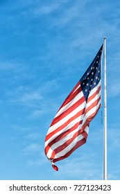 American flag waving on blue sky background in Key West, USA on sunny day. National symbol, citizenship and patriotism concept. Pride, freedom and unity.