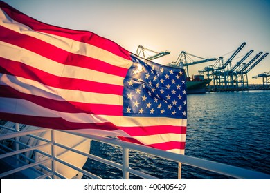 American Flag waving on a boat. Background: beautiful sunset and doc cranes in the port.