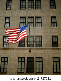An American flag waving on the facade of a building.