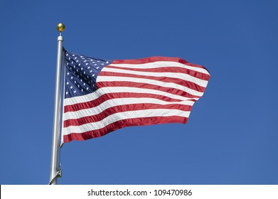 American flag waving on flagpole against blue sky in warm afternoon