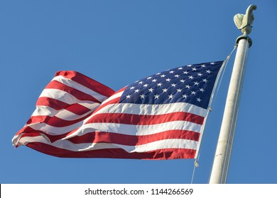 American flag waving on flagpole in clear sky