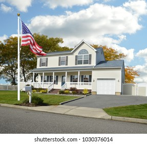 American Flag waving on front yard lawn of Suburban McMansion Home Blue Sky Clouds USA