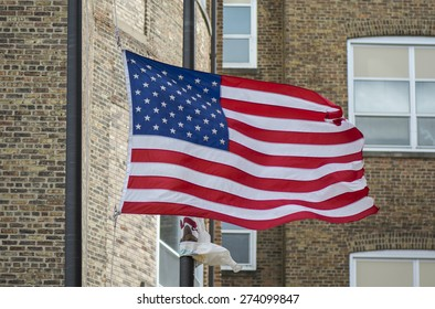 An American flag waving proudly in front of a tall brick building.