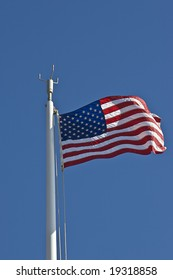 American flag waving in the wind against a blue sky in vertical orientation