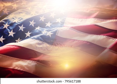 American flag waving in the wind at sunset or sunrise.