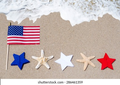 American flag with white, blue and red stars and starfishes on the sandy beach - USA holidays concept