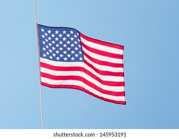 The American flag in the wind against the sky