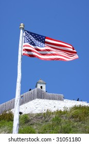 American Flag in the wind with an old Fort behind it