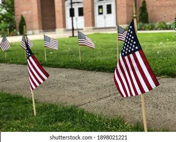 American Flags along Sidewalk by Brick Building Memorial Day