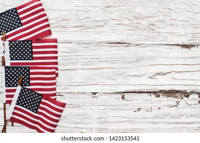 American Flags for the America's 4th of July Celebration over a white rustic background to mark America's Independence Day. Image shot from top view.