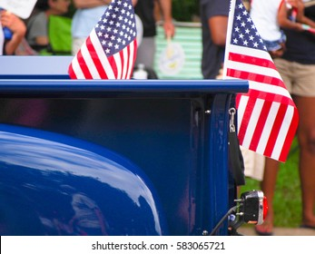 American flags attached to a bright blue classic truck driving in a Fourth of July parade.