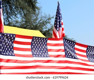 American flags with blue sky and the branches of a tree