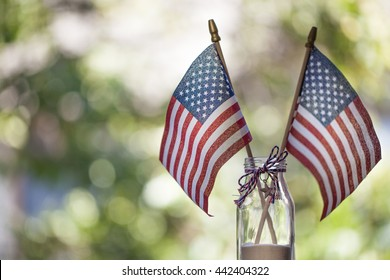 American flags with bokeh green background. July 4th celebration.