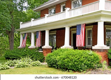 American flags decorating front porch of old brick home