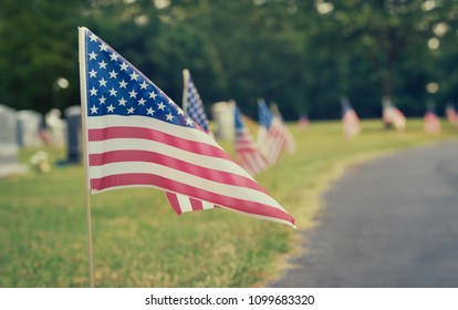 American flags displayed at a cemetery on Memorial Day. Vintage tone.