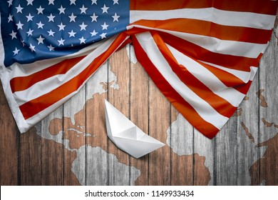 American flags and paper boat with wooden background. Columbus day concept