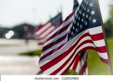 American flags in a row along sidewalk of suburb neighborhood for 4th of July celebration for Independence Day blurred background and focus on the front of the flag with wooden stick