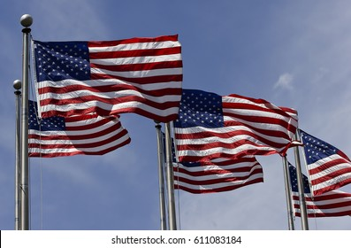 American flags waving on flagpoles against the blue sky