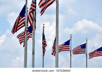 American flags waving in the wind on a blue sky day