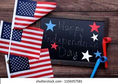 American flags and wooden frame with inscription Happy Independence Day