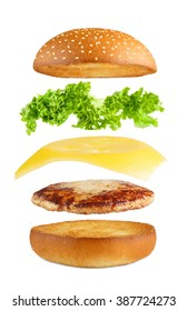 American food. Burger layers isolated. Separated burger layers isolated. Hamburger explosion. Cheeseburger flying fillings isolated at white background. Levitation of burger and cheese, meat, lettuce.