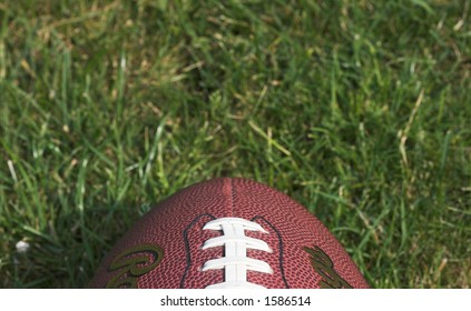 American football against a grass background