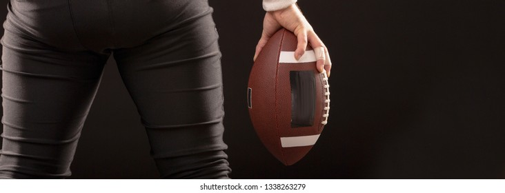 American Football Ball in hands of footballer on black background