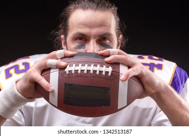 American Football Ball in hands of player on black background
