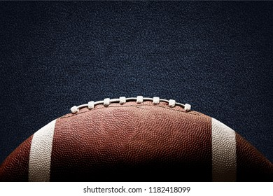 American football ball on black background illuminated