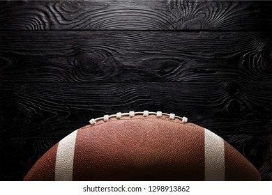 American football ball on black background illuminated by the light