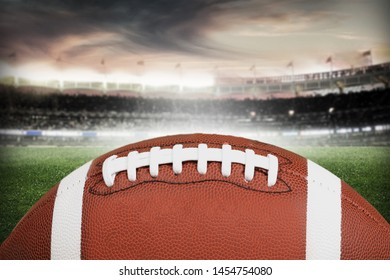 American football ball on stadium field background